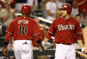 PHOENIX - MAY 26:  Mark Reynolds #27 of the Arizona Diamondbacks congratulates teammate Justin Upton #10 after he scored a sixth inning run against the San Diego Padres during the major league baseball game at Chase Field on May 26, 2009 in Phoenix, Arizo