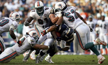 SAN DIEGO - DECEMBER 11:  Running back LaDainian Tomlinson #21 of the San Diego Chargers is tackeld by Zach Thomas #54 and Channing Crowder #52 of the Miami Dolphins during the Chargers 23-21 loss to the Dolphins during the 2nd half of their NFL Game on D