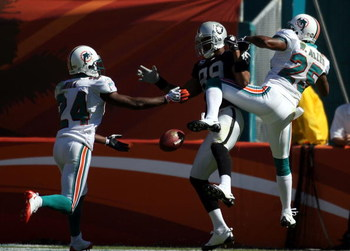 MIAMI - NOVEMBER 16:  Receiver Ronald Curry #89 of the Oakland Raiders is defended by safety Will Allen #25 and Renaldo Hill #24 of the Miami Dolphins in the second quarter at Dolphin Stadium November 16, 2008 in Miami, Florida. Miami defeated Oakland 17-