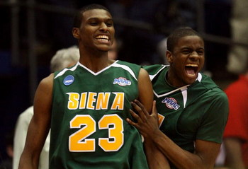DAYTON, OH - MARCH 20:  Edwin Ubiles #23 and Clarence Jackson #13 of the Siena Saints celebrate on the court after defeating the Ohio State Buckeyes in overtime during the first round of the NCAA Division I Men's Basketball Tournament at the University of