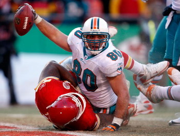 KANSAS CITY, MO - DECEMBER 21:  Receiver Anthony Fasano #80 of the Miami Dolphins raises the ball after scoring the game-winning touchdown as Tank Tyler #93 of the Kansas City Chiefs defends during the game on December 21, 2008 at Arrowhead Stadium in Kan