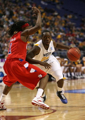 MINNEAPOLIS - MARCH 20:  Darryl Bryant #25 of the West Virginia Moutaineers drives against London Warren #1 of the Dayton Flyers during the first round of the NCAA Division I Men's Basketball Tournament at the Hubert H. Humphrey Metrodome on March 20, 200