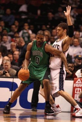 EAST RUTHERFORD, NJ - MARCH 04:  Brook Lopez  #11 of the New Jersey Nets guards Leon Powe  #0 of Boston Celtics during their game on March 4th, 2009 at The Izod Center in East Rutherford, New Jersey.  NOTE TO USER: User expressly acknowledges and agrees t