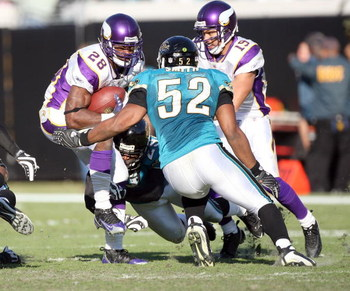 JACKSONVILLE, FL - NOVEMBER 23:  Andrian Peterson #28 of the Minnesota Vikings is tackled by Daryl Smith #52 of the Jacksonville Jaguars during the game at Jacksonville Municipal Stadium on November 23, 2008 in Jacksonville, Florida.  (Photo by Sam Greenw