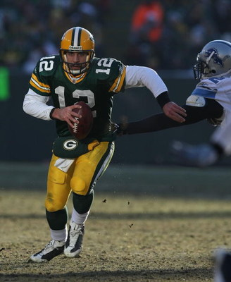 GREEN BAY, WI - DECEMBER 28: Aaron Rodgers #12 of the Green Bay Packers breaks away from Cliff Avril #92 of the Detroit Lions on December 28, 2008 at Lambeau Field in Green Bay, Wisconsin. The Packers defeated the Lions 31-21. (Photo by Jonathan Daniel/Ge
