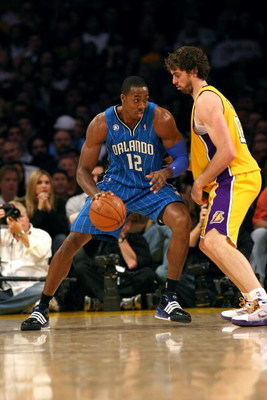 LOS ANGELES - JANUARY 16:  Dwight Howard #12 of the Orlando Magic dribbles the ball to the basket against Pau Gasol #16 of the Los Angeles Lakers during their NBA game on January 16, 2009 at Staples Center in Los Angeles, California. The Magic won 109-103