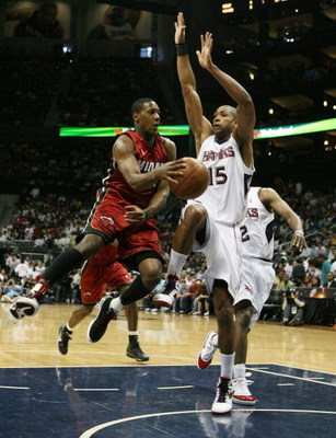 ATLANTA - MAY 03:  Mario Chalmers #6 of the Miami Heat passes around Al Horford #15 of the Atlanta Hawks during Game Seven of the Eastern Conference Quarterfinals at Philips Arena on May 3, 2009 in Atlanta, Georgia. The Hawks defeated the Heat 91-78. NOTE