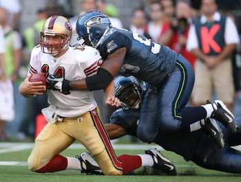 SEATTLE - SEPTEMBER 14:  Quarterback J.T. O'Sullivan #14 of the San Francisco 49ers is tackled by Lawrence Jackson #95 of the Seattle Seahawks after rushing for 12 yards in the fourth quarter on September 14, 2008 at Qwest Field in Seattle Washington. The