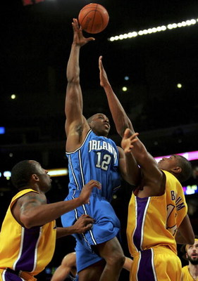 LOS ANGELES - JANUARY 12:  Dwight Howard #12 of the Orlando Magic goes up for a shot between Kobe Bryant #24 and Andrew Bynum #17 of the Los Angeles Lakers at Staples Center January 12, 2007 in Los Angeles, California. NOTE TO USER: User expressly acknowl