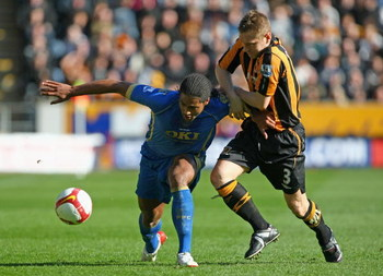 HULL, ENGLAND - APRIL 04:  Glen Johnson of Portsmouth challenges Andrew Dawson of Hull City during the Barclays Premier League match between Hull City and Portsmouth at the KC Stadium on April 4, 2009 in Hull, England.  (Photo by Clive Rose/Getty Images)