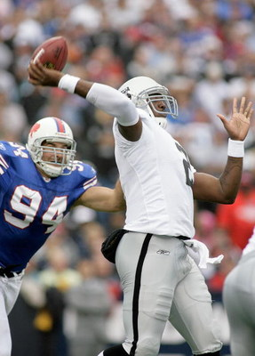 ORCHARD PARK, NY - SEPTEMBER 21: JaMarcus Russell #2 of the Oakland Raiders throws a pass with pressure from Aaron Schobel #94 of the Buffalo Bills on September 21, 2008 at Ralph Wilson Stadium in Orchard Park, New York. Buffalo won 24-23. (Photo by Rick