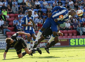 WIGAN, ENGLAND - MAY 24:  Titus Bramble (R) of Wigan heads away from Hermann Hreidarsson of Portsmouth during the Barclays Premier League match between Wigan Athletic and Portsmouth at the JJB Stadium on May 24, 2009 in Wigan, England.  (Photo by Hamish B