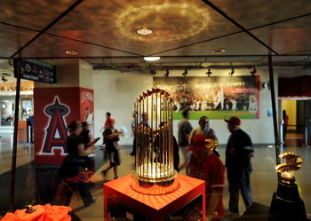 ANAHEIM, CA - APRIL 06:  Fans look at the 2002 World Series trophy of Los Angeles Angels at Angels Stadium of Anaheim after the gates opened for the Los Angeles Angels home opener against the Oakland Athletics on opening day April 6, 2009 in Anaheim, Cali