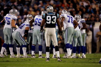 HARLOTTE, NC - OCTOBER 29:  Defensive end Mike Rucker #93 of the Carolina Panthers waits at the line of scrimmage as the Dallas Cowboys huddle during the game on October 29, 2006 at Bank of America Stadium in Charlotte, North Carolina. The Cowboys won 35-