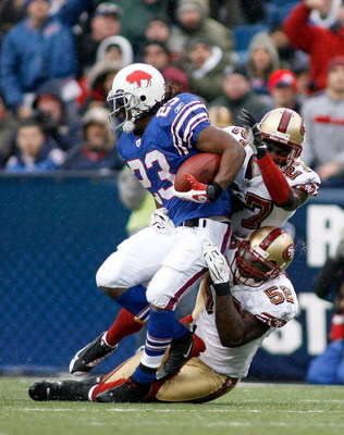 ORCHARD PARK, NY - NOVEMBER 30: Marshawn Lynch #23 of the Buffalo Bills is tackled by Walt Harris #27 and Patrick Willis #52 of the San Francisco 49ers  on November 30, 2008 at Ralph Wilson Stadium in Orchard Park, New York. The 49ers won 10-3.  (Photo by