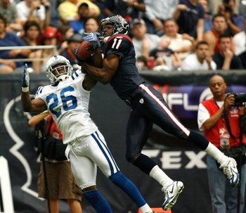 HOUSTON - SEPTEMBER 23:  Wide receiver Jerome Mathis #11 of the Houston Texans leaps for a reception over defensive back Kelvin Hayden #26 of the Indianapolis Colts in the third quarter  September 23, 2007 at Reliant Stadium in Houston, Texas.  (Photo by