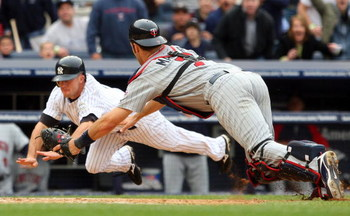 NEW YORK - MAY 17:  Joe Mauer #7 of the Minnesota Twins dives to tag out Brett Gardner #11 of the New York Yankees in the ninth inning on May 17, 2009 at Yankee Stadium in the Bronx borough of New York City. The Yankees defeated the Twins 3-2 in ten innin