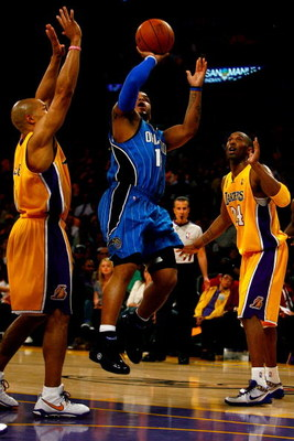 LOS ANGELES, CA - JUNE 04:  Jameer Nelson #14 of the Orlando Magic goes up for a shot over Derek Fisher #2 and Kobe Bryant #24 of the Los Angeles Lakers in Game One of the 2009 NBA Finals at Staples Center on June 4, 2009 in Los Angeles, California. NOTE