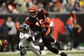 CINCINNATI - NOVEMBER 27:  Wide receiver Chris Henry #15 of the Cincinnati Bengals evades cornerback Deion Sanders #37 of the Baltimore Ravens during the game on November 27, 2005 at Paul Brown Stadium in Cincinnati, Ohio. Cincinnati won the game, 42-29.