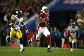 TAMPA, FL - FEBRUARY 01:  Larry Fitzgerald #11 of the Arizona Cardinals runs for yards after the catch on a 64-yard touchdown reception against James Harrison #92 and Bryant McFadden #20 of the Pittsburgh Steelers in the fourth quarter during Super Bowl X
