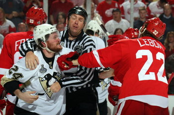 DETROIT - JUNE 06:  Linesman Pierre Racicot breaks up a scuffle between Matt Cooke #24 of the Pittsburgh Penguins and Brett Lebda #22 of the Detroit Red Wings during Game Five of the 2009 NHL Stanley Cup Finals at Joe Louis Arena on June 6, 2009 in Detroi