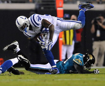 JACKSONVILLE, FL - DECEMBER 18:  Dominic Rhodes #38 of the Indianapolis Colts is tripped up during the game against the Jacksonville Jaguars at Jacksonville Municipal Stadium on December 18, 2008 in Jacksonville, Florida.  (Photo by Sam Greenwood/Getty Im