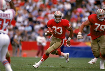 SAN FRANCISCO - OCTOBER 22:  Running back Roger Craig #33 of the San Francisco 49ers looks for room to run against the New England Patriots defense during a game at Candlestick Park on October 22, 1989 in San Francisco, California.  The 49ers won 37-20.