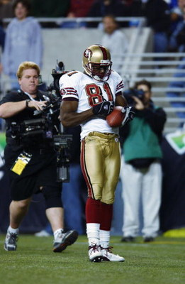 SEATTLE - OCTOBER 14:  Wide receiver Terrell Owens #81 of the San Francisco 49ers pulls a pen out of his sock and signs the football after scoring a touchdown against the Seattle Seahawks during their game on October 14, 2002 at Seahawks Stadium in Seattl