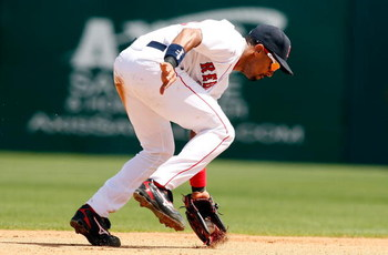 FORT MYERS, FL - MARCH 08:  Shortstop Julio Lugo #23 of the Boston Red Sox stops a ground ball against the Tampa Bay Rays during a Grapefruit League Spring Training Game at City of Palms Park on March 8, 2009 in Fort Myers, Florida.  (Photo by J. Meric/Ge