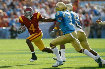 PASADENA, CA - DECEMBER 06:  Joe McKnight #4 of the USC Trojans runs away from Rahim Moore #3 and  Reggie Carter #51 of the UCLA Bruins during the game on December 6, 2008 at the Rose Bowl in Pasadena, California.  (Photo by Harry How/Getty Images)