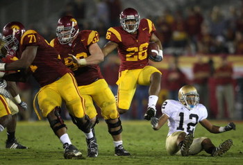 LOS ANGELES, CA - NOVEMBER 29:  Tailback Marc Tyler #26 of the USC Trojans runs past Robert Blanton #12 of the Notre Dame Fighting Irish during the game against at the Memorial Coliseum on November 29, 2008 in Los Angeles, California. USC defeated Notre D
