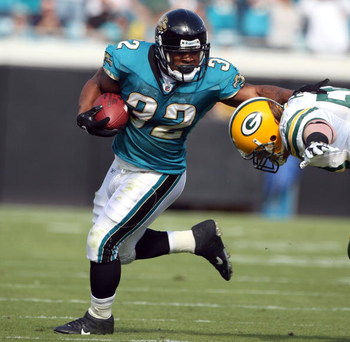 JACKSONVILLE, FL - DECEMBER 14:  A. J. Hawk #50 of the Green Bay Packers attempts to tackle Maurice Jones-Drew #32 of the Jacksonville Jaguars during the game at Jacksonville Municipal stadium on December 14, 2008 in Jacksonville, Florida.  (Photo by Sam