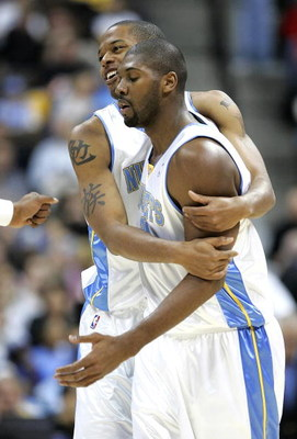 DENVER - DECEMBER 6:  Marcus Camby #23 bear hugs Nene #31 of the Denver Nuggets after putting up a run against Orlando Magic in the first half on December 6, 2004 at the Pepsi Center in Denver, Colorado.  NOTE TO USER: User expressly acknowledges and agre