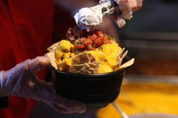 MILWAUKEE - APRIL 10:  A worker prepares nachos for a customer before the Opening Day game between the Milwaukee Brewers and the Chicago Cubs on April 10, 2009 at Miller Park in Milwaukee, Wisconsin. (Photo by Jonathan Daniel/Getty Images)