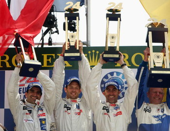 LE MANS, FRANCE - JUNE 14:  Peugeot drivers Marc Gene, Alex Wurz and David Brabham celebrate on the podium after winning the Le Mans 24h race on June 14, 2009 in Le Mans, France.  (Photo by Bryn Lennon/Getty Images)