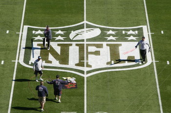 TAMPA, FL - JANUARY 31:  Workers paint the NFL logo on center field a day before Super Bowl XLIII between the Arizona Cardinals and the Pittsburgh Steelers on January 31, 2009 at Raymond James Stadium in Tampa, Florida.  (Photo by Win McNamee/Getty Images