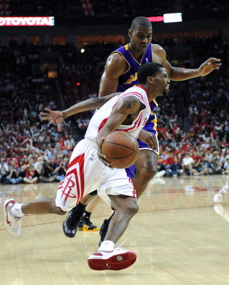 HOUSTON - MAY 10:  Guard Aaron Brooks #0 of the Houston Rockets dribbles the ball past Andrew Bynum #17 of the Los Angeles Lakers in Game Four of the Western Conference Semifinals during the 2009 NBA Playoffs at Toyota Center on May 10, 2009 in Houston, T