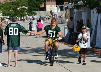 GREEN BAY, WI - JULY 28: Brady Poppinga #51 of the Green Bay Packers shakes hands with a fan as he rides a bicycle to practice before a summer training camp practice on July 28, 2008 at the Hutson Center in Green Bay, Wisconsin. (Photo by Jonathan Daniel/