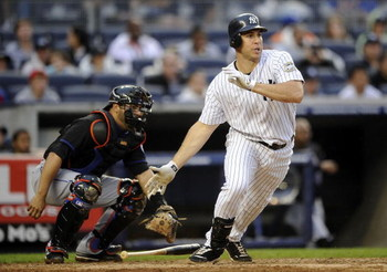 NEW YORK - JUNE 13:  Mark Teixeira #25 of the New York Yankees swings in front of Omir Santos #9 the New York Mets on June 13, 2009 at Yankee Stadium in the Bronx Borough of New York City.  (Photo by Jeff Zelevansky/Getty Images)