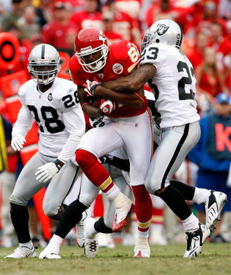 KANSAS CITY, MO - SEPTEMBER 14:  Receiver Dwayne Bowe #82 of the Kansas City Chiefs carries the ball upfield after making a reception as DeAngelo Hall #23 and Gibril Wilson #28 of the Oakland Raiders defend during the first half of the game on September 1