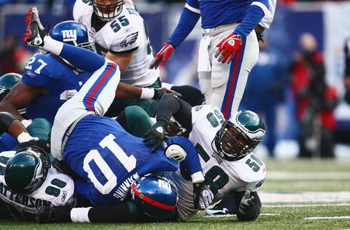 EAST RUTHERFORD, NJ -  JANUARY 11:  Eli Manning #10 of the New York Giants is tackled by Mike Patterson #98 and Trent Cole #58 of the Philadelphia Eagles during the NFC Divisional Playoff Game on January 11, 2009 at Giants Stadium in East Rutherford, New