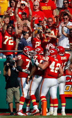 KANSAS CITY, MO - SEPTEMBER 28:  Fans cheer as teammates congratulate Larry Johnson #27 of the Kansas City Chiefs after Johnson rushed for a touchdown during the fourth quarter of the game against the Denver Broncos on September 28, 2008 at Arrowhead Stad