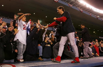 NEW YORK - OCTOBER 20:  Mike Myers #36 of the Boston Red Sox celebrates with the fans after defeating the New York Yankees 10-3 to win game seven of the American League Championship Series on October 20, 2004 at Yankee Stadium in the Bronx borough of New