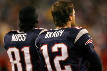 FOXBOROUGH, MA - DECEMBER 23: Randy Moss #81 and Tom Brady #12 of the New England Patriots stand on the sideline against the Miami Dolphins at Gillette Stadium on December 23, 2007 in Foxborough, Massachusetts. Patriots won 28-7. (Photo by Jim Rogash/Gett