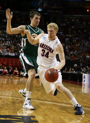 MIAMI - MARCH 22:  Forward Chase Budinger #34 of the University of Arizona Wildcats is defended by center Chris Moore #42 of the Cleveland State University Vikings during the second round of the NCAA Division I Men's Basketball Tournament at the American