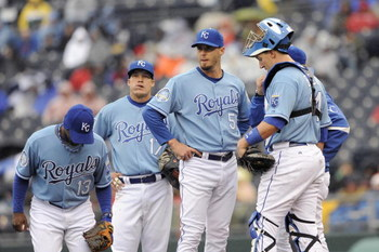 KANSAS CITY, MO - APRIL 12:  Pitcher Gil Meche #55 of the Kansas City Royals stands with teammates on the mound against the New York Yankees on April 12, 2009 at Kauffman Stadium in Kansas City, Missouri. (Photo by G. Newman Lowrance/Getty Images)