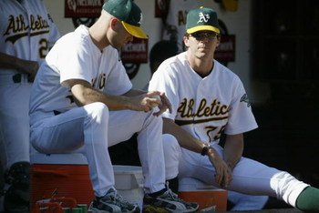OAKLAND, CA - OCTOBER 6:  Tim Hudson #15 and Barry Zito #75 of the Oakland Athletics watch from the dugout during game five of the American League Western Division Series against the Minnesota Twins at Network Associates Coliseum on October 6, 2002 in Oak