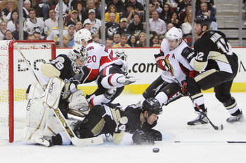 PITTSBURGH - APRIL 11: Goaltender Marc-Andre Fleury #29 of the Pittsburgh Penguins keeps his eyes on the puck as Brooks Orpik #44 of the Penguins slides into Fleury and Antoine Vermette #20 of the Ottawa Senators leaps in front of Fleury during game two o