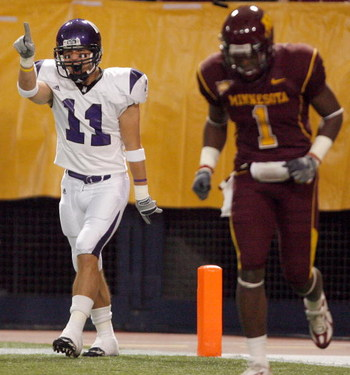 MINNEAPOLIS - NOVEMBER 01:  Jeremy Ebert #11 of the Northwestern Wildcats celebrates his touchdown for a 7-0 lead in front of Tramaine Brock #1 of the Minnesota Golden Gophers during the first quarter at the Hubert H.Humphrey Metrodome on November 1, 2008