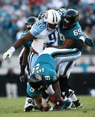 JACKSONVILLE, FL - NOVEMBER 16: Quarterback David Garrard #9 of the Jacksonville Jaguars fumbles as he is sacked by defensive tackle Albert Haynesworth #92 of the Tennessee Titans while he is blocked by offensive lineman Khalif Barnes #69 at Jacksonville